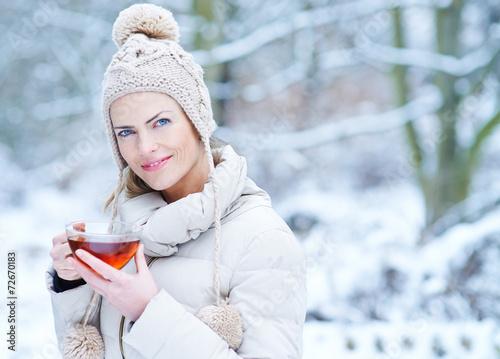 canvas print picture Frau trinkt Tasse Tee im Winter im Schnee