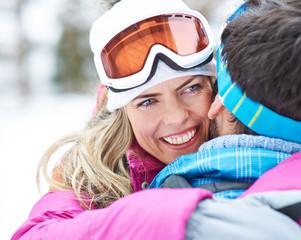 Frau umarmt Mann im Winter beim Skifahren