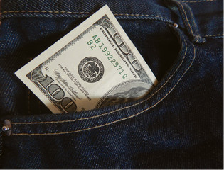 banknote of one hundred dollars in dark blue jeans pocket
