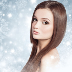Young attractive brunette woman in a snow. Winter beauty concept