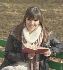 Student girl reading book on bench in autumn forest