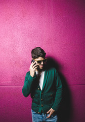 Model man talking with a smart phone over fuchsia background