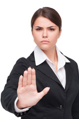 Serious young business woman doing stop gesture