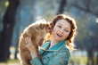 Pomeranian dog and  red haired woman playing outdoor