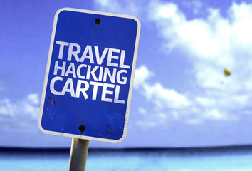 Travel Hacking Cartel sign with a beach on background
