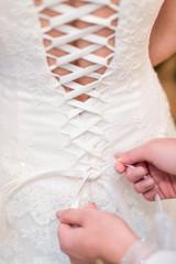 bridesmaid tying knot on wedding dress