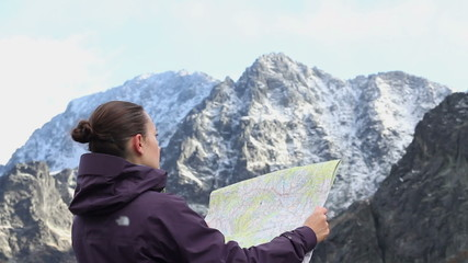 Young woman reading map on trial in mountains, Tatras, Slovakia