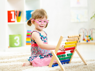 child girl with eyeglasses playing abacus toy