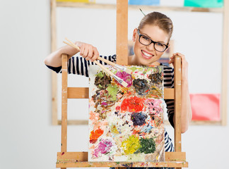 Smiling female painter standing behind easel with palette