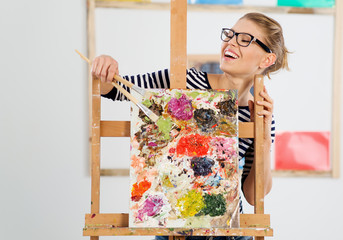 Laughing female painter showing her colorful artwork