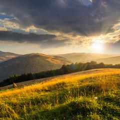 field on hillside near village at sunset