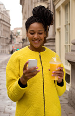young woman reading a text and holding a smoothie.