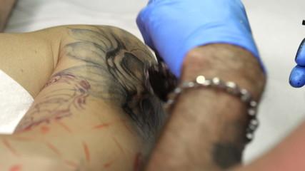 Tattoo artist tattooing a skull