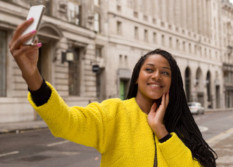 young woman taking a selfie in the street.
