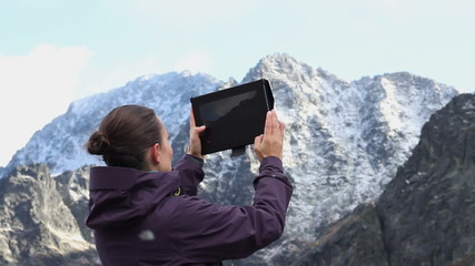 Woman hiker taking photo with digital tablet, Tatras, Slovakia