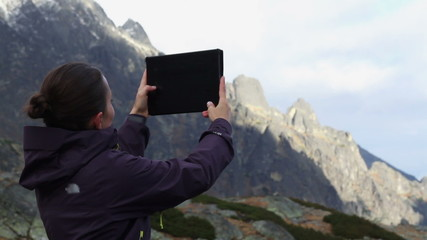 Young woman taking pictures on a tablet, Tatras, Slovakia