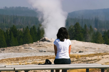 A woman waiting for eruption of a geyser