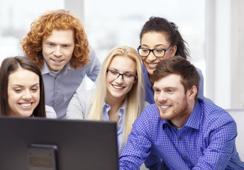 smiling business team looking at computer monitor