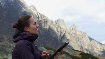Young woman is using a tablet pc in the mountains