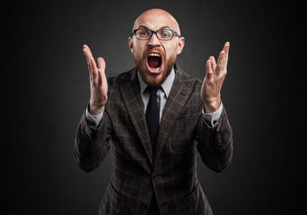 Man with glasses, a beard, shouting. Widely puts hands.