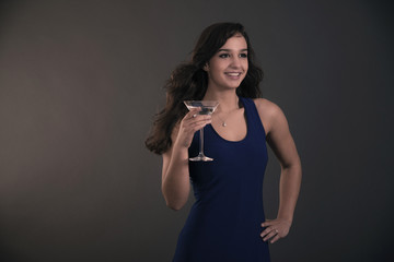 Pretty brunette teenage girl holding cocktail glass wearing blue