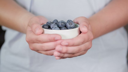 female teen hand show bowl full of blueberries, made from raw