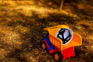 Hardhat on the back of a toy dumpster truck
