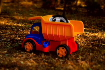 Colorful plastic toy dumpster truck outdoors