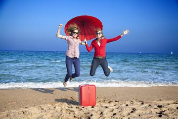 Hermanas gemelas con sombrilla roja saltando en la playa
