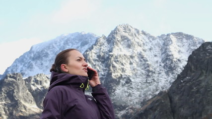 Woman talking on cellphone in the mountains