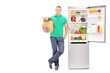 Young man standing by an open refrigerator