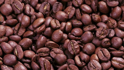 close up footage of rotating roasted coffee beans some zoom