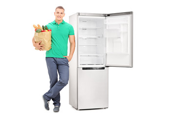 Man with grocery bag standing by an empty fridge