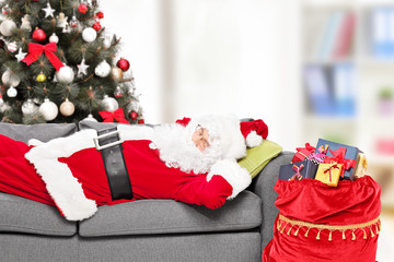 Santa Claus sleeping by a Christmas tree at home