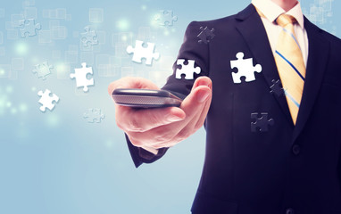 Businessman with puzzle over cellphone