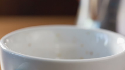 close up footage of milk pourink into espresso, making latte art