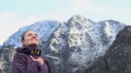 Young woman breathing fresh air in winter mountains