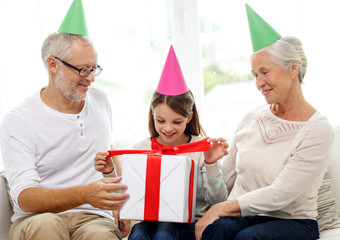 smiling family in party hats with gift box at home