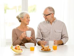 happy senior couple having breakfast at home