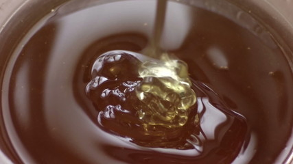 honey flowing from dipper, close up