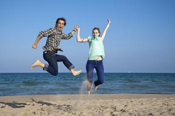 Pareja de novios saltando en la playa de forma divertida