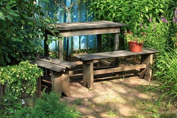 wooden bench with flower pots in a wild garden