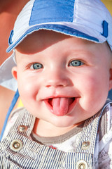baby boy is sticking out tongue at people