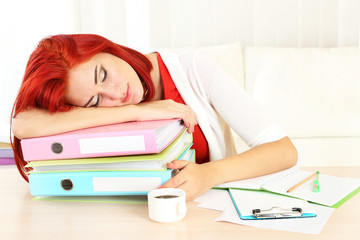 Tired girl with many folders sleeps on table