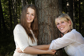 Environmental Portrait of two women hugging a tree in a forest