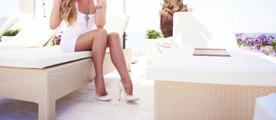 Woman legs on a sun lounger on a beach.