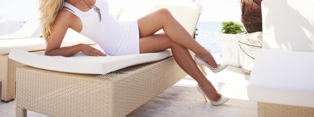 Woman legs on a sun lounger.