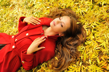 Woman in red coat lying in autumn leaves.