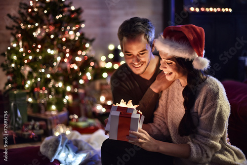 Leinwanddruck Bild portrait of a young couple in their living room in  christmas ev