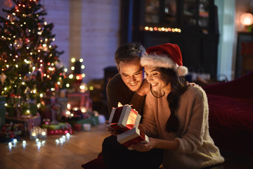 portrait of a young couple in their living room at christmas eve